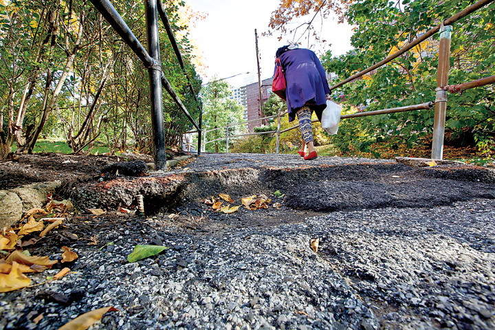 Holes riddle an uphill walking path near 609 Kappock St. Residents say the path has been in poor condition for more than a decade, causing stumbles and other problems. Orange paint in the most dangerous parts is intended to warn seniors and people pushing strollers.
