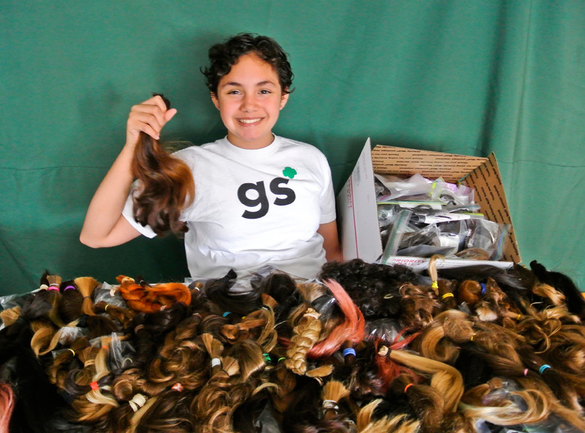 Girl Scout Marieteresa Porcher Allen displays the results of her drive to collect hair for wigs for young people who have lost their hair due to burns, chemotherapy or other reasons. Marieteresa, 11, reached more than double the goal she set to earn a Girl Scout Silver Award — the highest award for Girl Scout Cadettes — receiving 239 donations via mail and from city hair salons by the middle of this month. Other members of North Riverdale Girl Scout Troop 1477 are doing remarkable things, like Maya Bliffeld's (age 11) project to donate books for a new library in Guatemala; Laura McEntire's (11) coat drive for people in Breezy Point still affected by Hurricane Sandy; Sophia Moore's (12) project to help women in Togo; and Faith Mulismanaj's (12) plans to paint the benches