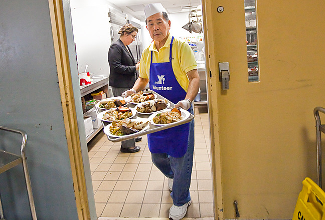 The giving season unofficially begins with Thanksgiving week and volunteers like Duffy Chen, 79, served an early Thanksgiving lunch at The Riverdale Y Senior Center on Tuesday.