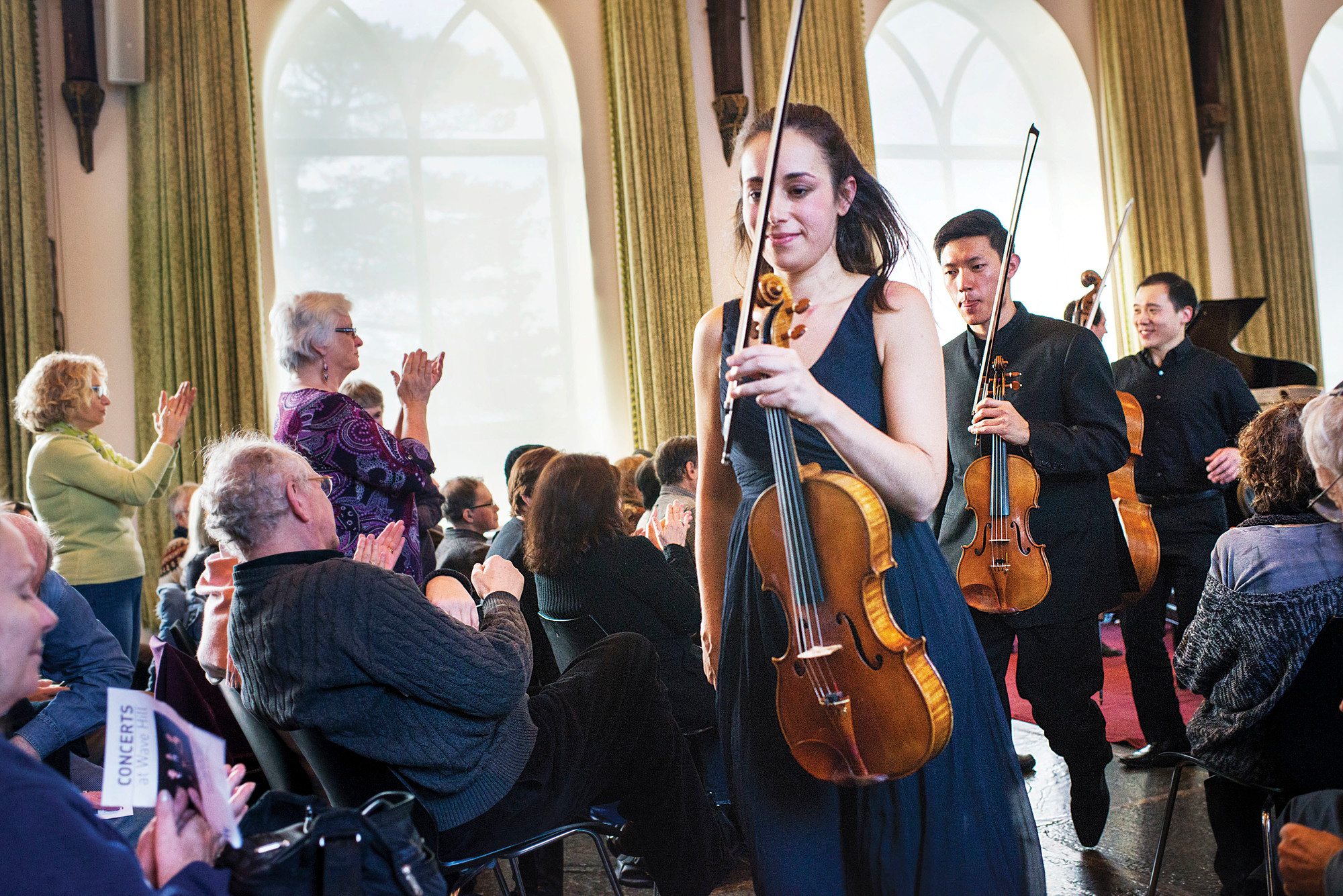 Violist Jessica Bodner leads fellow musicians Daniel Chong and Kee-Hyun Kim out of the concert hall.