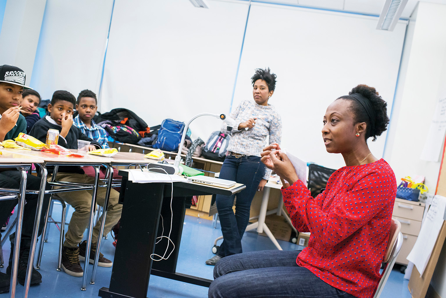 English teacher Keedra Gibba, 37, left, leads an after school discussion on an upcoming class trip to Ghana with students and Accra, Ghana native Julia Boahene, a Fieldston parent.