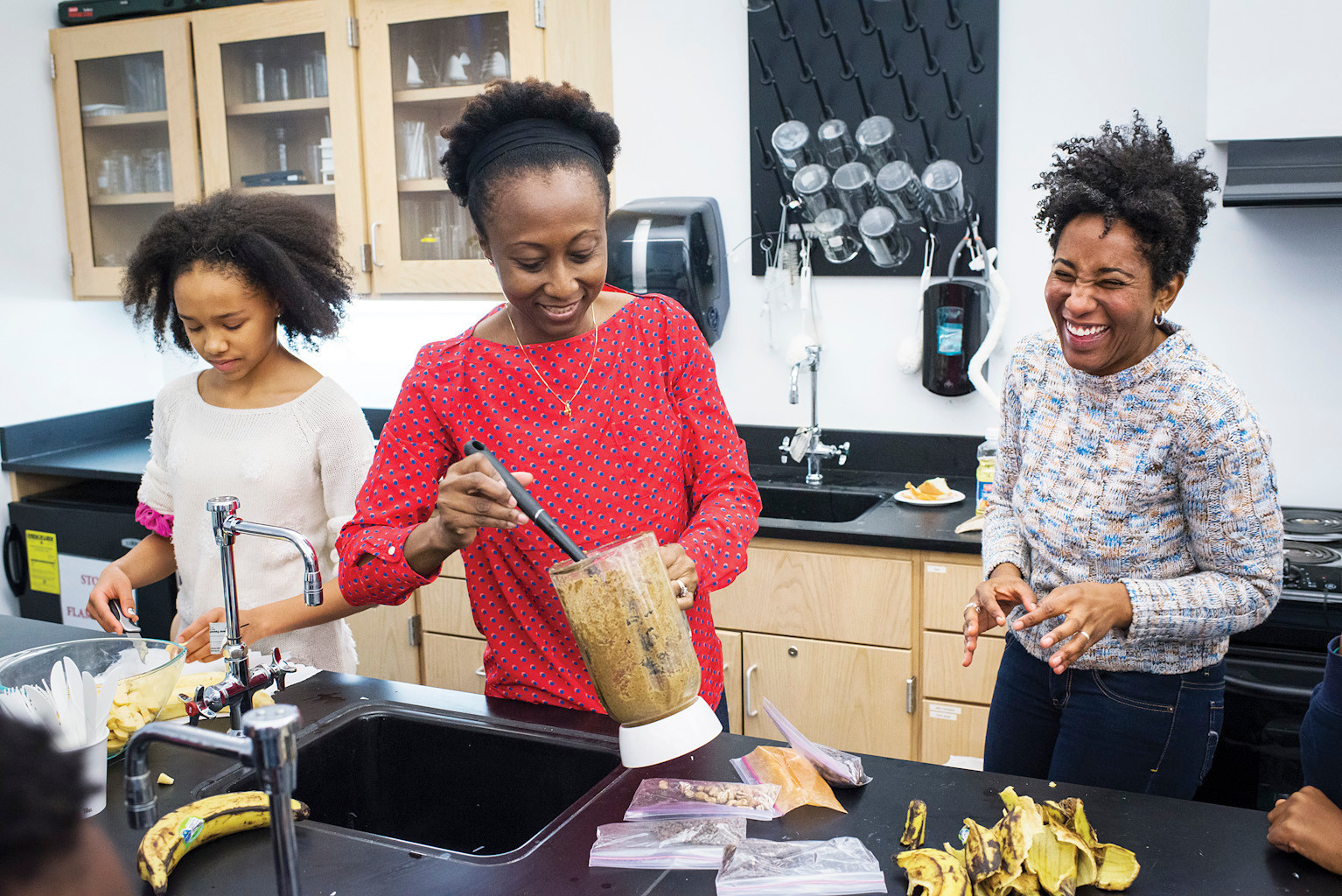 English teacher Keedra Gibba, 37, right, helps make the Ghanaian dish Kelewele with parent and native Ghanaian Julia Boahene, center, alongside eighth grader Whitney Wyche, 13, at the Ethical Culture Fieldston School on Monday.