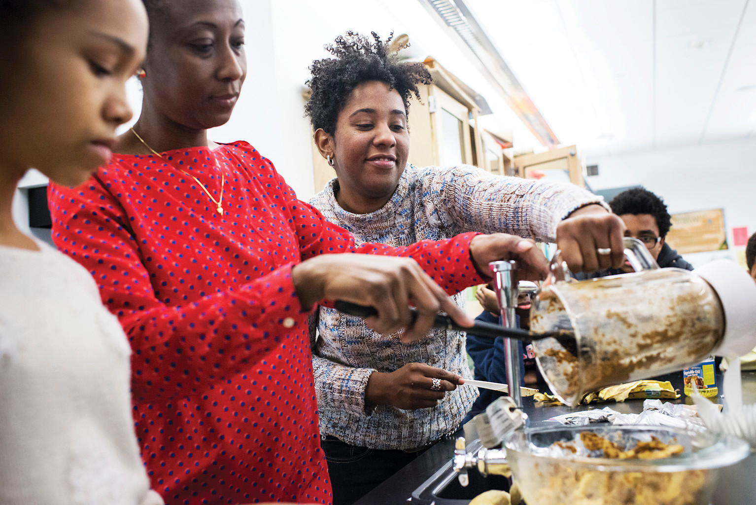 English teacher Keedra Gibba, 37, right, helps make the Ghanaian dish Kelewele with parent and native Ghanaian Julia Boahene, alongside eighth grader Whitney Wyche, 13.
