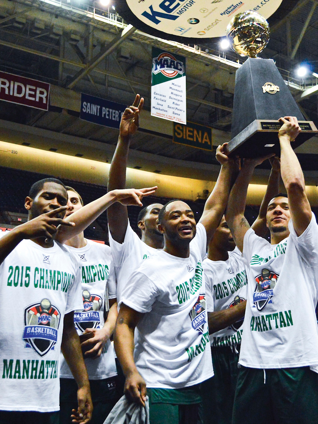 Manhattan College basketball players lift the MAAC Championship trophy after defeating Iona 79-69, securing a spot in the NCAA tournament in Albany on Sunday.