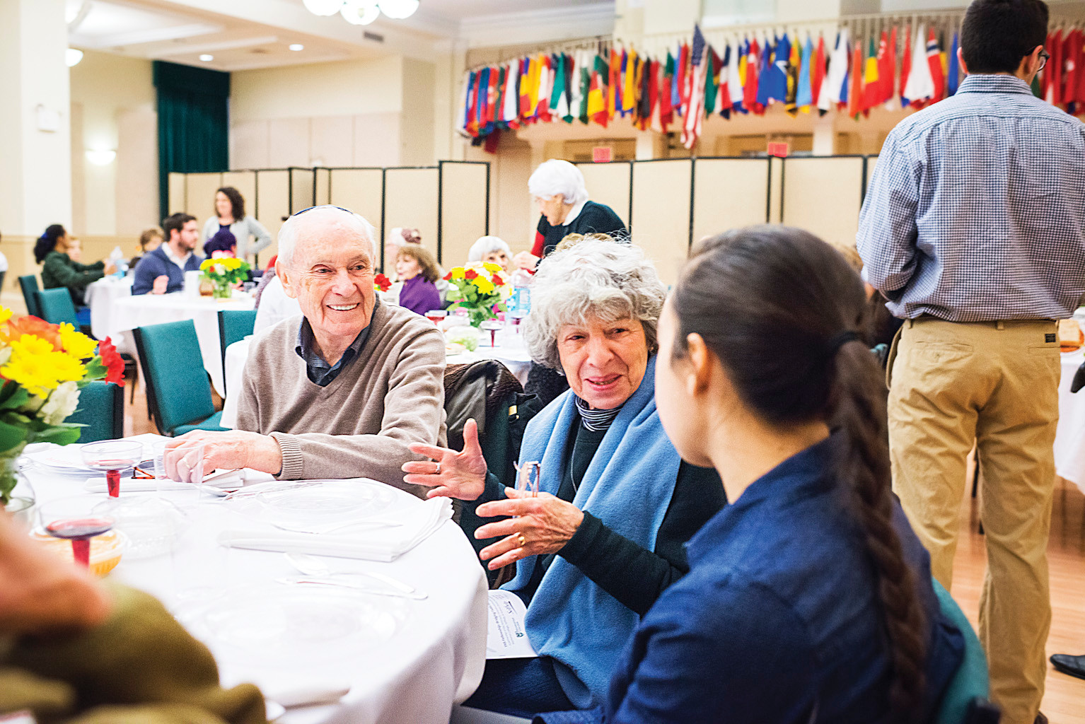 Riverdalian Faye Lieman, in the scarf, talks with students and fellow attendees at the Manhattan College seder celebration 'Bridging Faiths with Yeshiva Chovevei Torah' on Wednesday.
