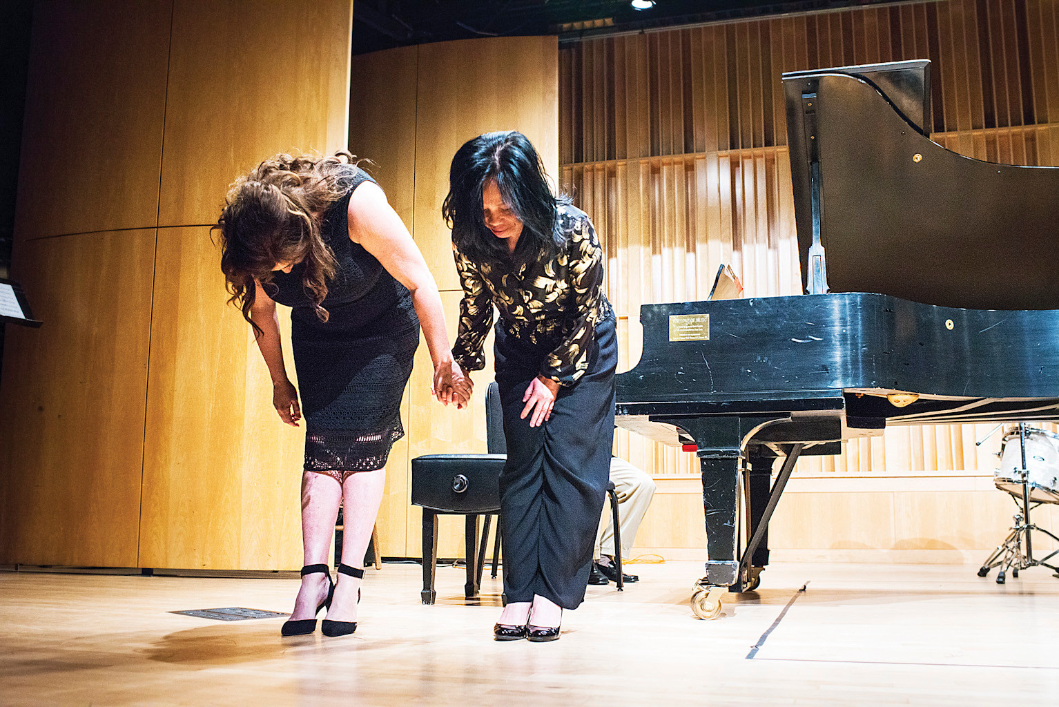 Pianists Claudia Knafo and Mira Ma are applauded in the school's auditorium after performing in a Hilltop Cares charity concert.