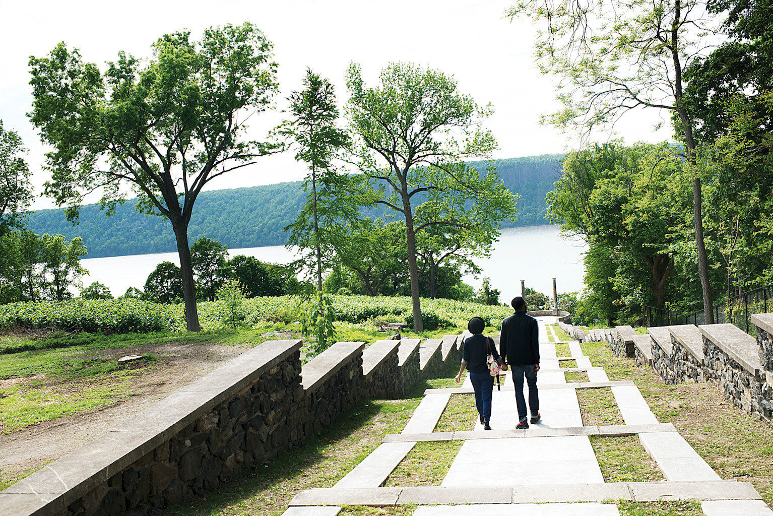 A young couple takes the stairs leading to a viewing platform called the Overlook, offering views of the Hudson River and Palisades.