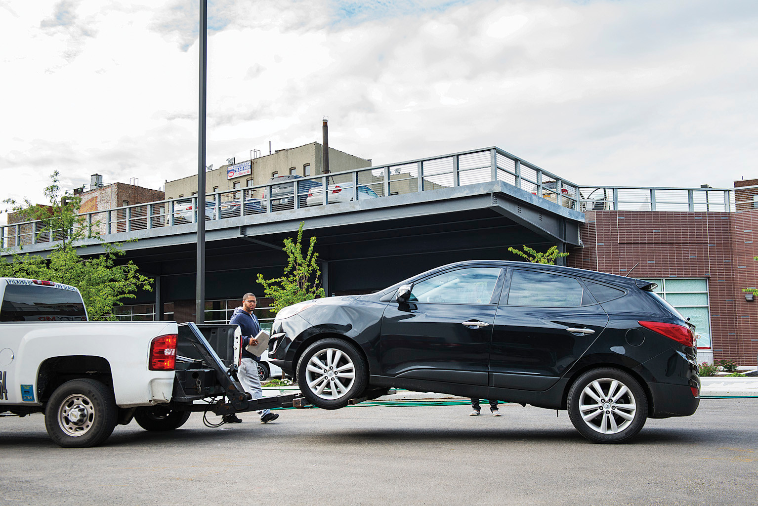A Hyundai SUV is towed from the parking lot at the new PetCo parking lot in Kingsbridge on June 4.
