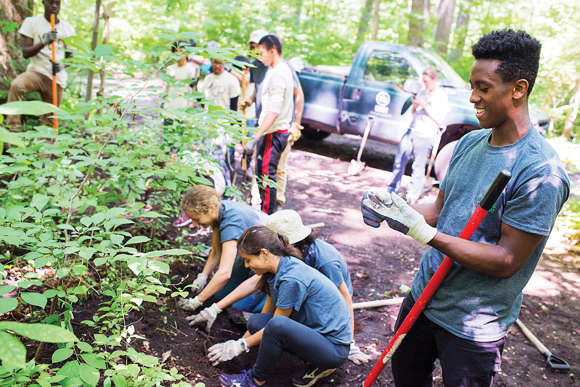 Kenyah Wiggins, a Truman High School student who lives in Coop City, helps to clear mud and weeds from an overgrown trail in Van Cortlandt Park on July 16.