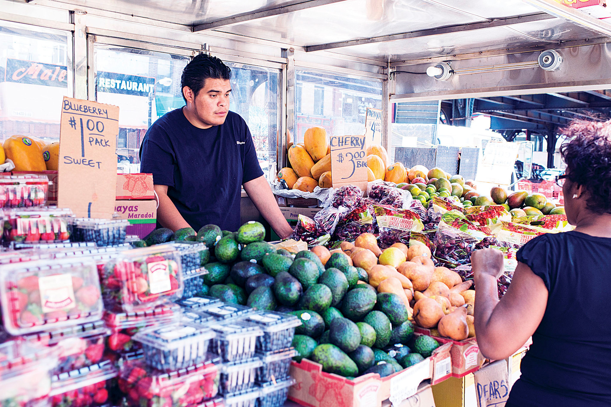Vendor Rogelio Espinoza, 25, sells fruit to Luisa Ortiz, 40, on July 16 near Broadway and West 231st Street.
