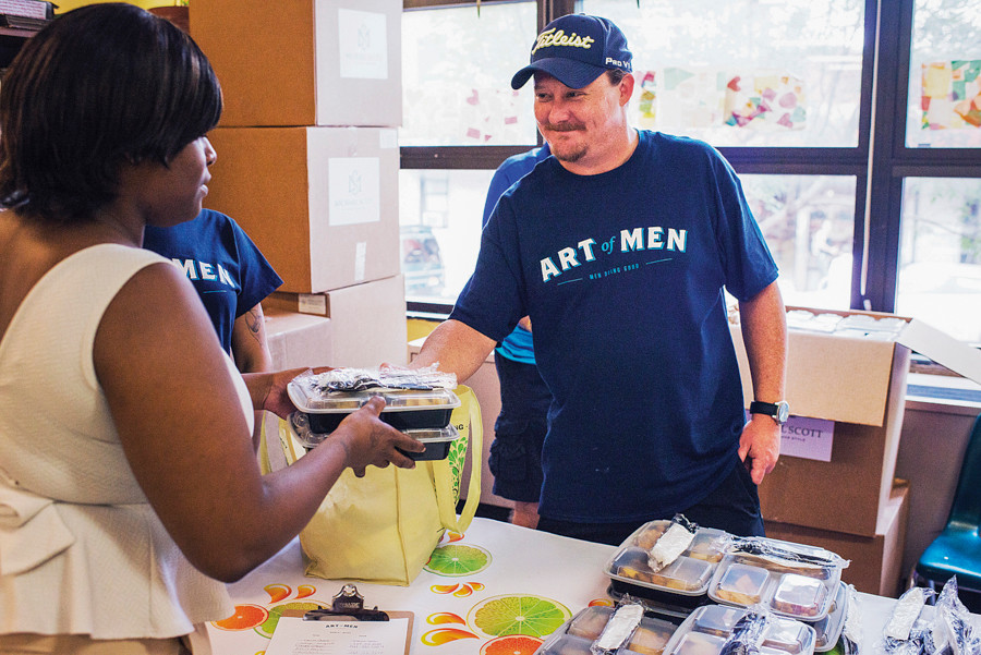 Patrick Caraher, 37, hands out free meals at the Montefiore Medical Community Center as part of the Art of Men volunteer organization.