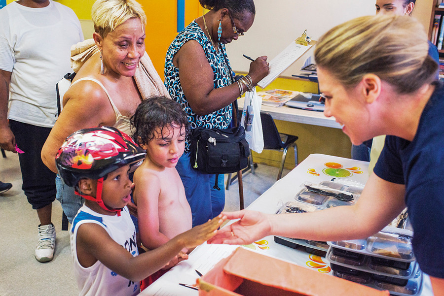 Jadeen Otero, 4, and Joel Abreu, 5, are greeted by volunteers from the organization Art of Men at a free meal pickup in the Montefiore Medical Community Center on July 29.