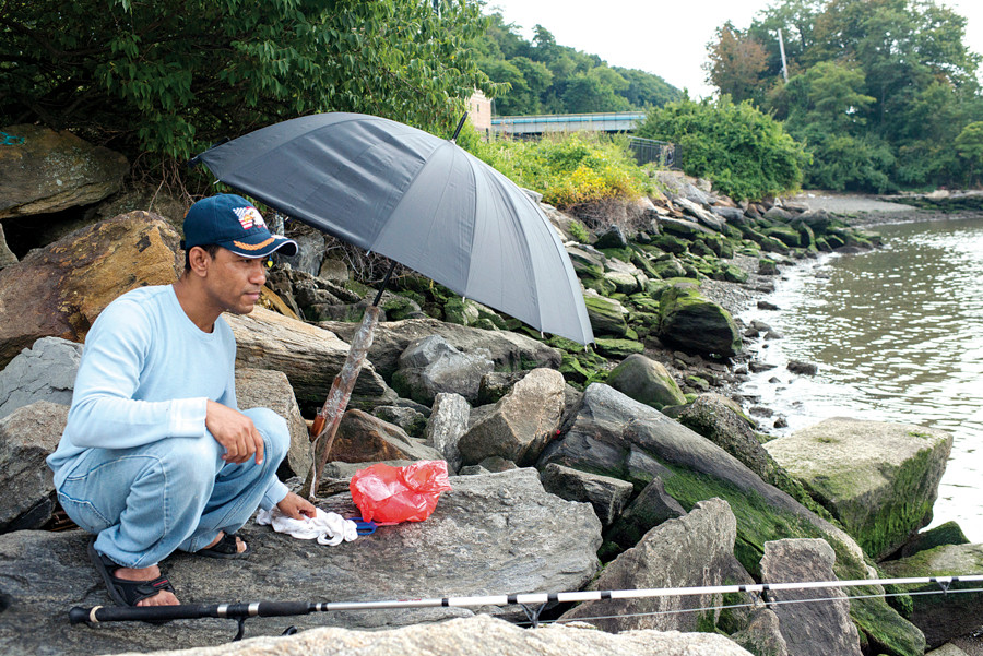 David Taca, an immigrant from Vietnam who speaks little English, fishes next to a Combined-Sewage Overflow pipe on the Hudson River, near the Riverdale Metro-North Station on Aug. 30.