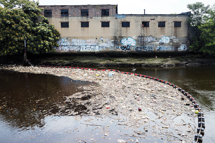 A floating boom catches trash and debris floating in the lower Bronx River next to Concrete Plant Park on Aug. 8.