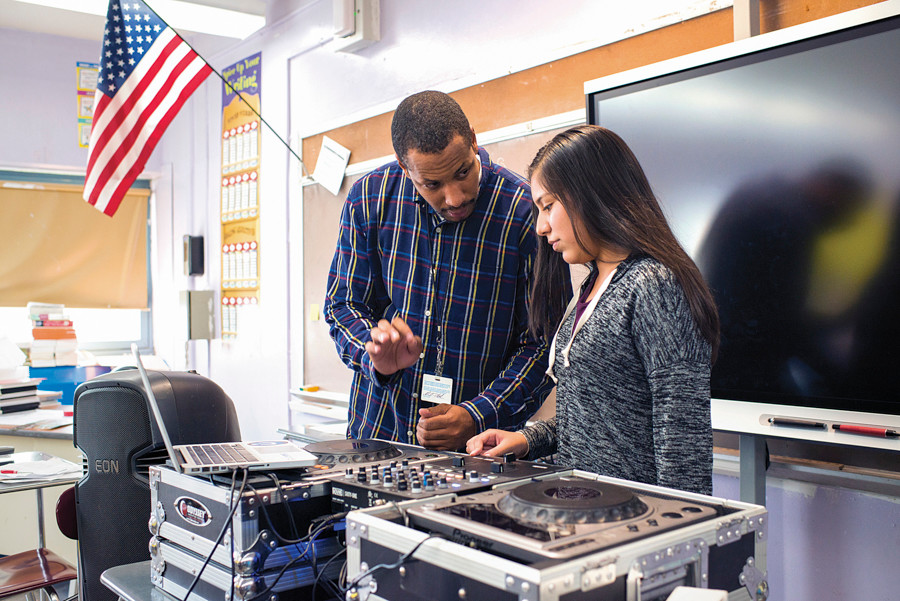 Michael 'DJ Uneeq' Patrick helps a student at NSLA/M.S. 244 with the turntables in a DJ class after school on Sept. 25.