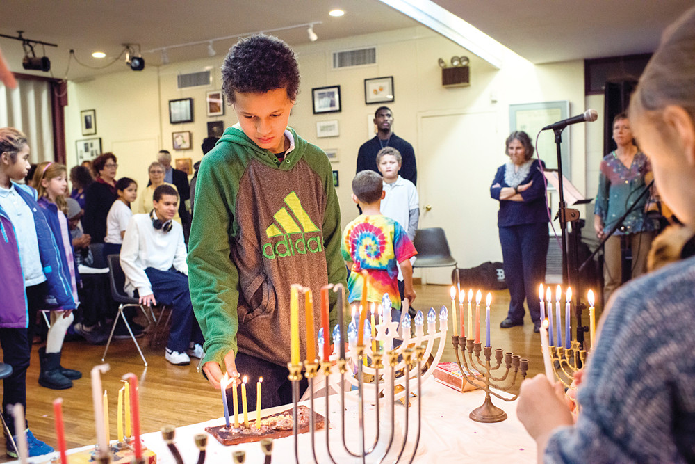 Haqq Coulibably, aged 12, lights a menorah candle during an interfaith gathering at the Society for Ethical Culture in Fieldston on Dec. 9.