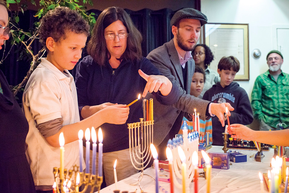 Hamid Coulibably, aged 10, lights a menorah candle during an interfaith gathering at the Society for Ethical Culture in Fieldston on Dec. 9.