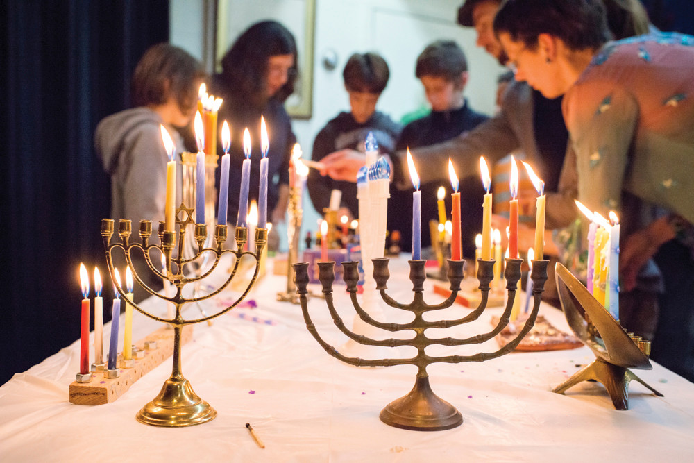 Members of the Society for Ethical Culture light menorah candles during an interfaith gathering in Fieldston on Dec. 9.