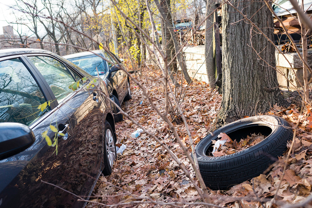 Trash and discarded tires line the curb along Manhattan College Parkway at Delafield Avenue, seen on Monday afternoon.