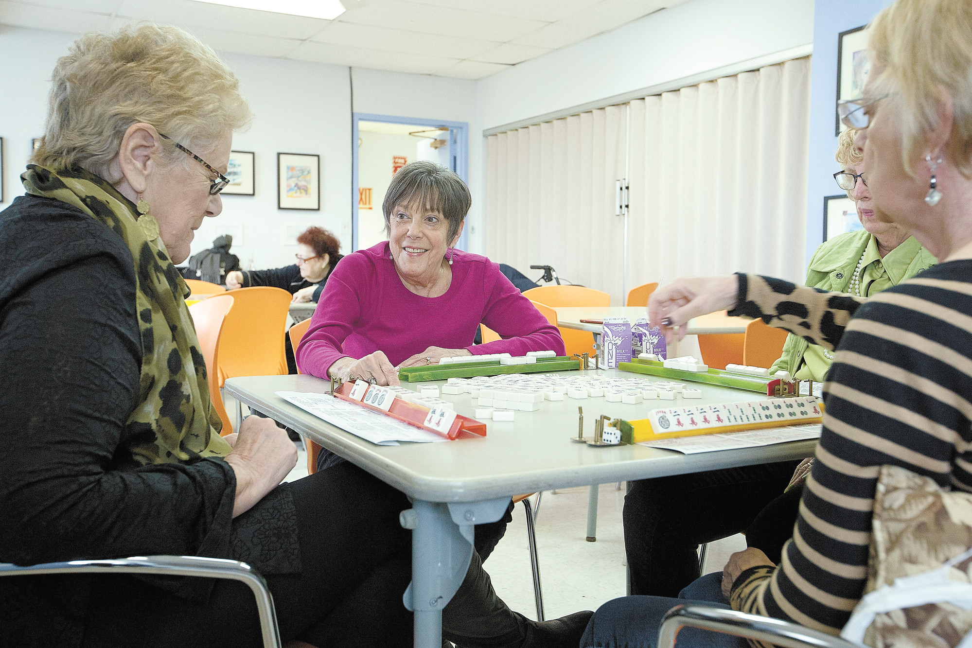 A group of women plays mahjong at Riverdale Senior Services on Monday.