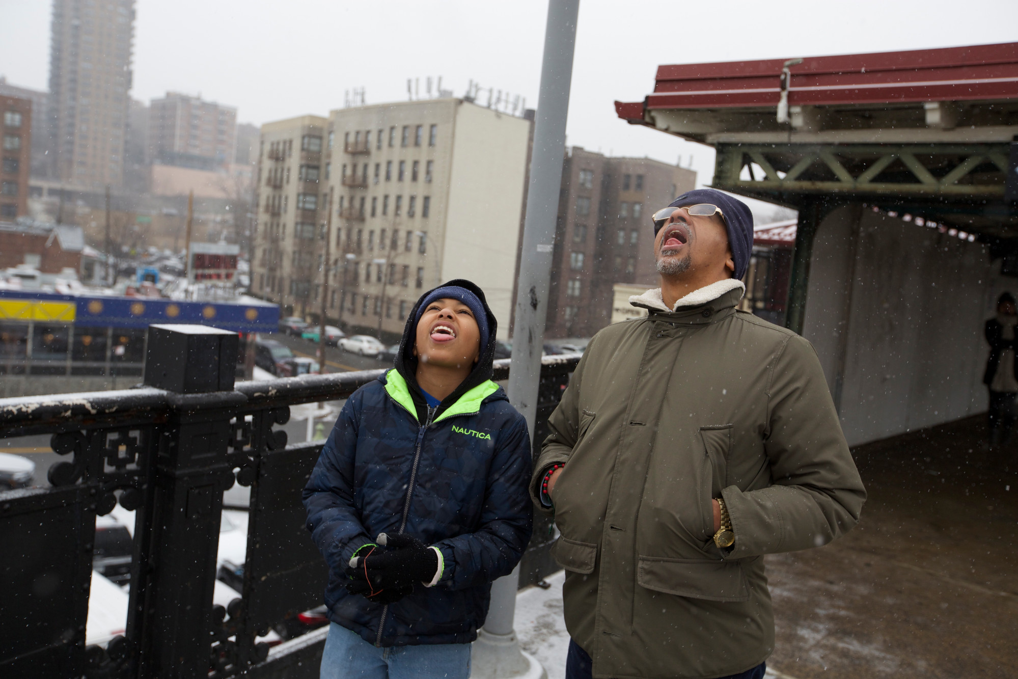 Jorge Piña, 56, and his son Jorge Piña, 11, stick their tongues out to catch snowflakes while they wait for the 1 Train at West 238th Street on Monday.