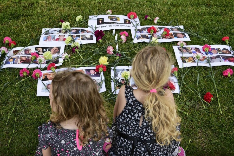 Grace and Hannah Born-Napolitano at a makeshift memorial for the victims, paces away from the vigil at the courthouse.