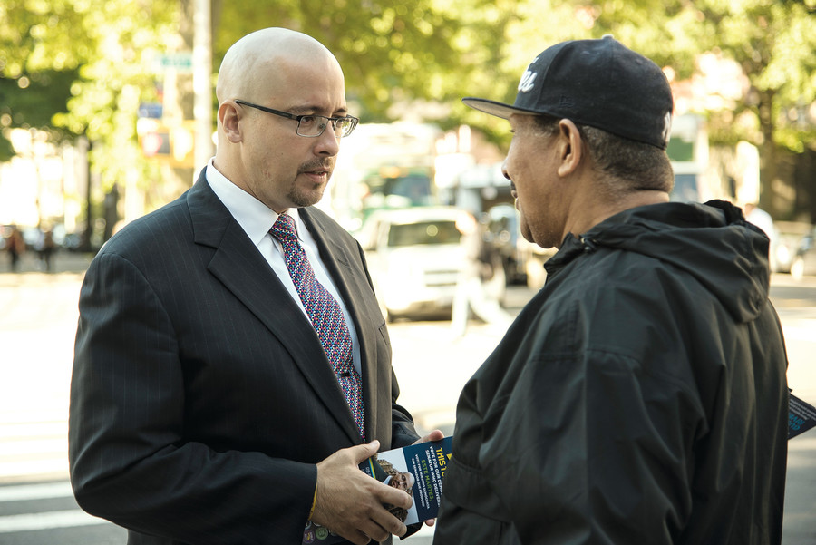 State Senator Gustavo Rivera talks with a voter outside a polling station.