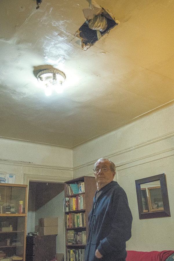 Tenant John Cawley stands under a gaping hole in his home's ceiling that has been left unrepaired for more than two years.