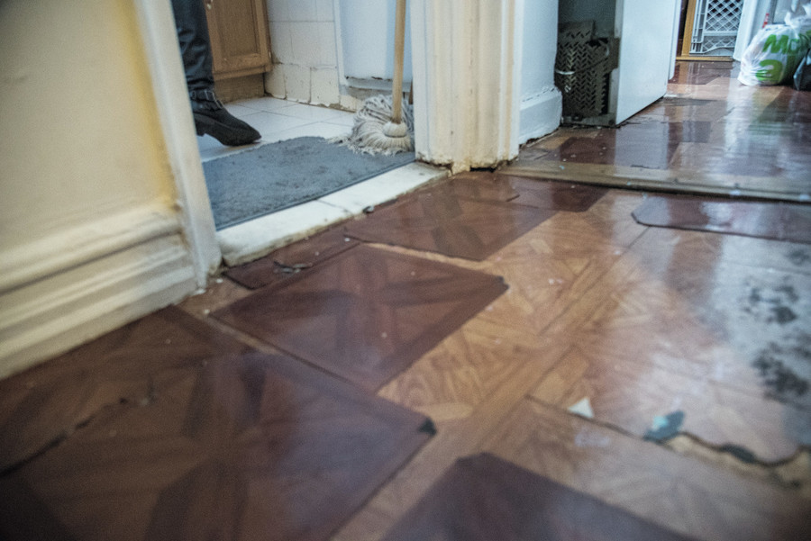 The floor in Jasmine Cabrera's apartment at 99 Marble Hill Ave., is littered with broken and loose tiles.  Hse has taken her landlord to court three times over rent and repair issues.
