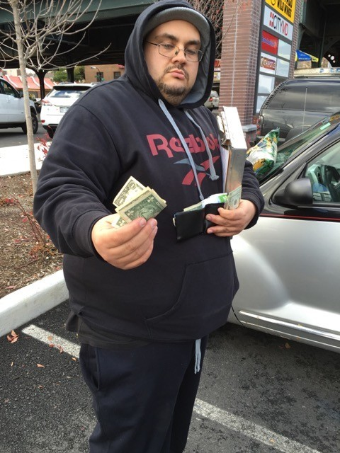 A tow truck operator of the All Boro towing company accepts a cash payment from a driver in the parking lot of a shopping center, in this photo submitted by Nancy Wertsch.