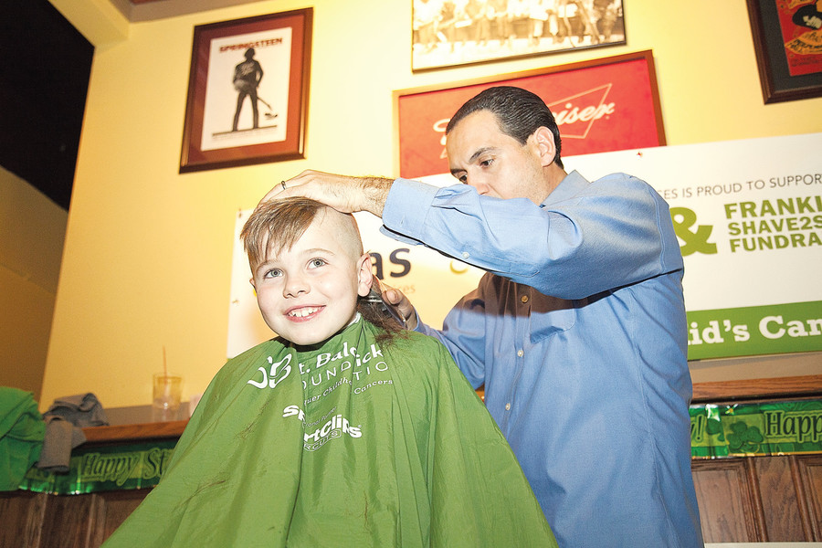 Shane Speckman, 8, has his head shaved by Tony Dulaj as part of a March 12 fundraiser for cancer research.