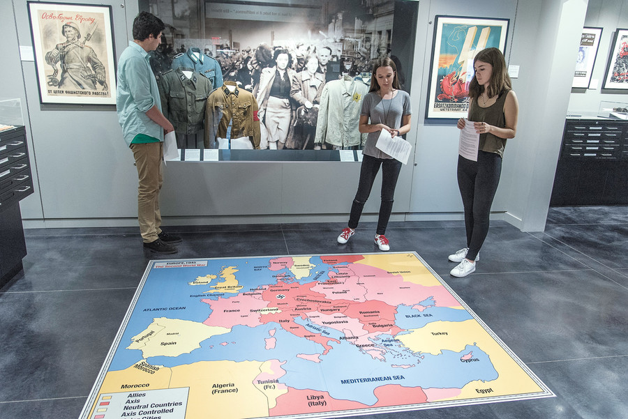 Student guides Alanna Ross and Mary Hripcsak at the Holocaust museum at the Bronx High School of Science tell the history of World War II in Europe, while another student guide, Evan Strauss, studies an exhibit.