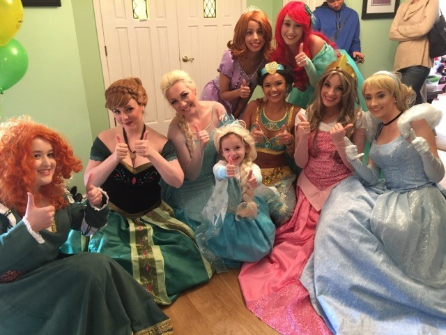 Kylee McGrane, dressed as Elsa from Frozen, and Margaret McAndrew, dressed as her sister Anna, third and second from left, co-founded the nonprofit A Moment of Magic. They are among volunteers who visit ill children.