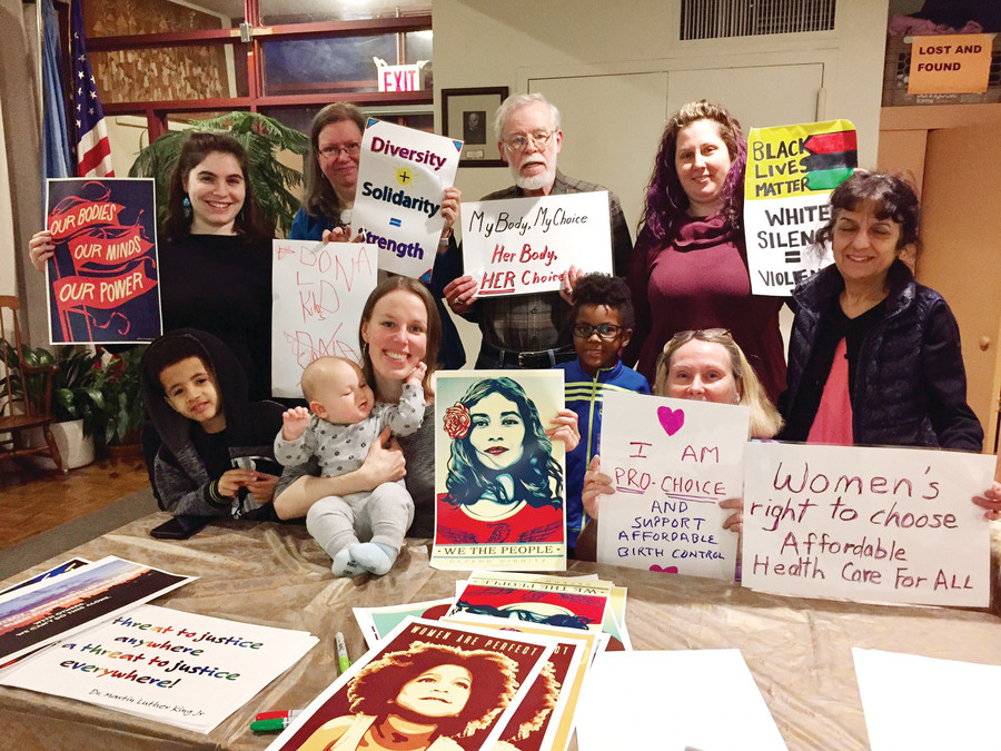 Local residents hold the signs they made for the women's marches in Washington and New York. The gathering was hosted by the Riverdale-Yonkers Society for Ethical Culture.