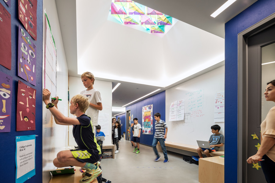 A student is writing on one of the new building's 'writeable walls.' The hallways were designed so that learning could take place inside and outside of the classroom.