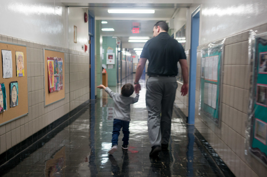 Steven Schwartz walks with his three-year-old son Jordan on his shoulders inside PS24.
