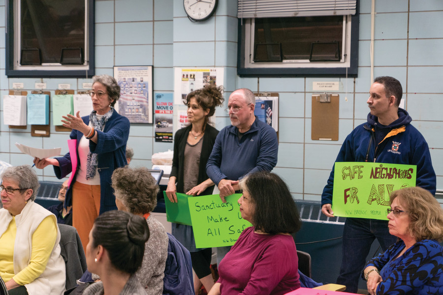 Lauren Chenven, speaking at left, a member of the grassroots organization Northwest Bronx People Power, introduces the group at the meeting of the 50th precinct community council.