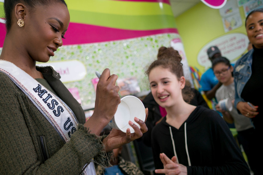 Miss USA signs a cup for Sophia Kereselize at Menchie's.