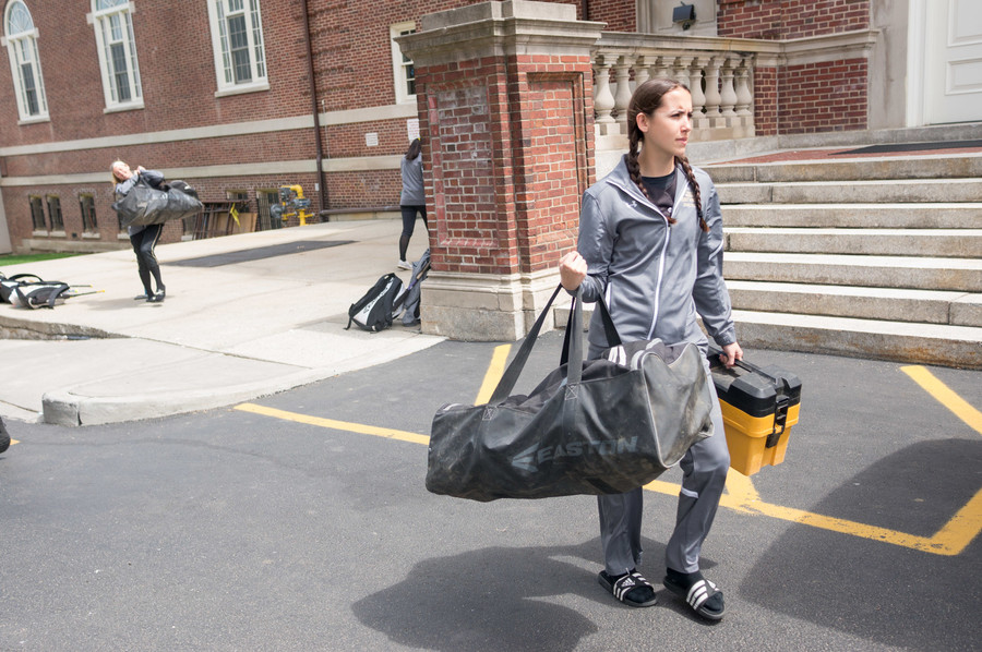 Members of the College of Mount Saint Vincent softball team carry their equipment to the van. The team has never played a home game because they don't have their own field.