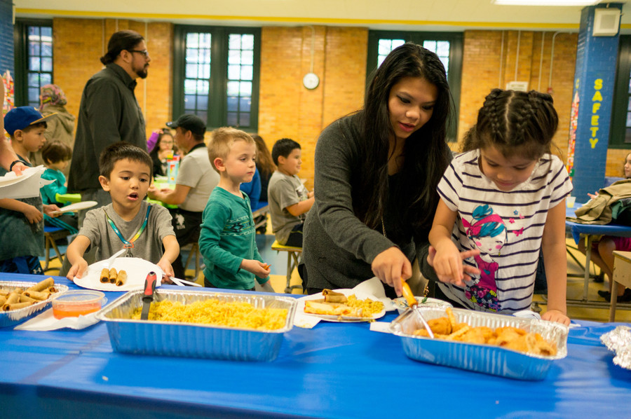 Reinalyn Rosario helps her children, Victoria and Eric, get food at P.S. 81's annual international dinner and raffle. Rosario also is a 1997 P.S. 81 graduate and was happy that the school continued the tradition.