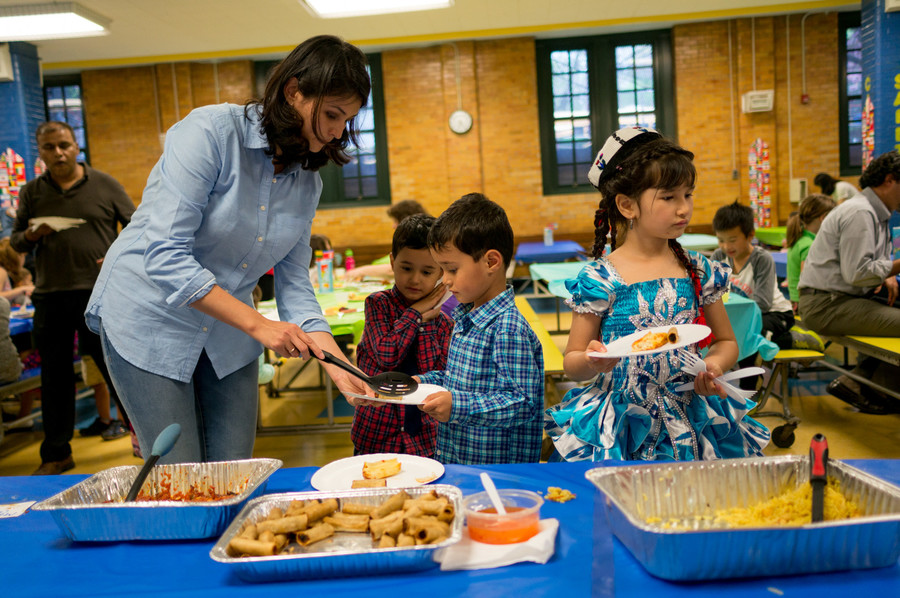 Farmangez Hikmat, left, helps her two sons get food at the annual international dinner raffle at the Robert J. Christen School, P.S. 81. Students and parents had a chance to experience other cultures through good food.