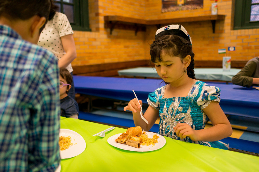 Armita Hikmat considers the plate of food at P.S. 81's annual international dinner and raffle. Dinner attendees could chose from a wide variety of cuisines.