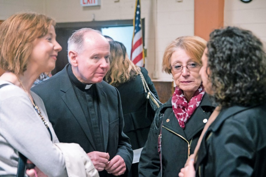 Monsignor Robert Larkin, center, of the Church of Saint Augustine in Larchmont, converses with some of the school's alumni. He previously served as the pastor of the Visitation School for 22 years.
