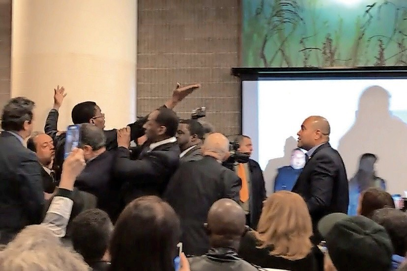 Self-proclaimed journalist and activist Sami Disu is escorted out of a speech by U.S. Rep. Adriano Espaillat after he rushed the podium. The congressman stopped security from doing so and answered Disu's questions during the event last week at Tracey Towers.