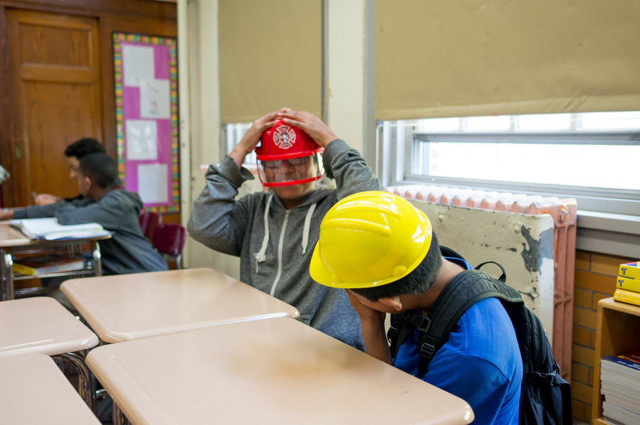 seventh-graders get into character as they take part in their last practice session for the Thurgood Marshall Mock Trial Competition. Some of the props included a police badge, firefighter's hat and construction worker's hat.