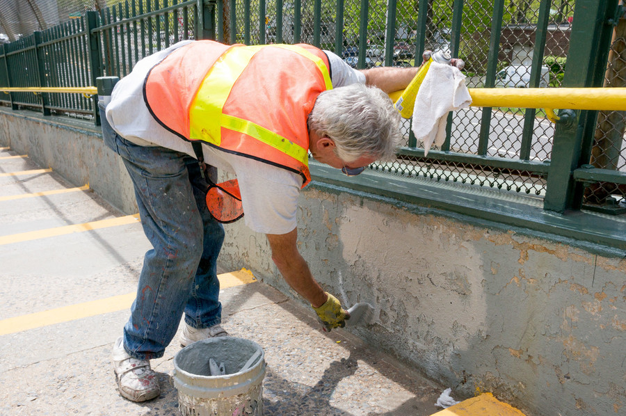 John Provetto paints over a tag on the pedestrian bridge near 235th Street.