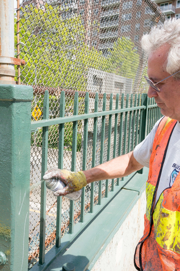 John Provetto sprays over tags on the pedestrian bridge near 235th Street. He has cans of paint that match the various surfaces he cleans.