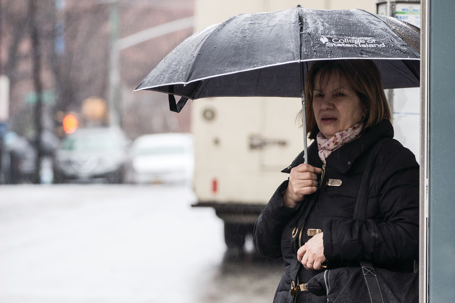A woman waits in the rain for a bus. Nearly 70 government officials have joined forces to push Gov. Andrew Cuomo to make much-needed improvements to the city's transit system.