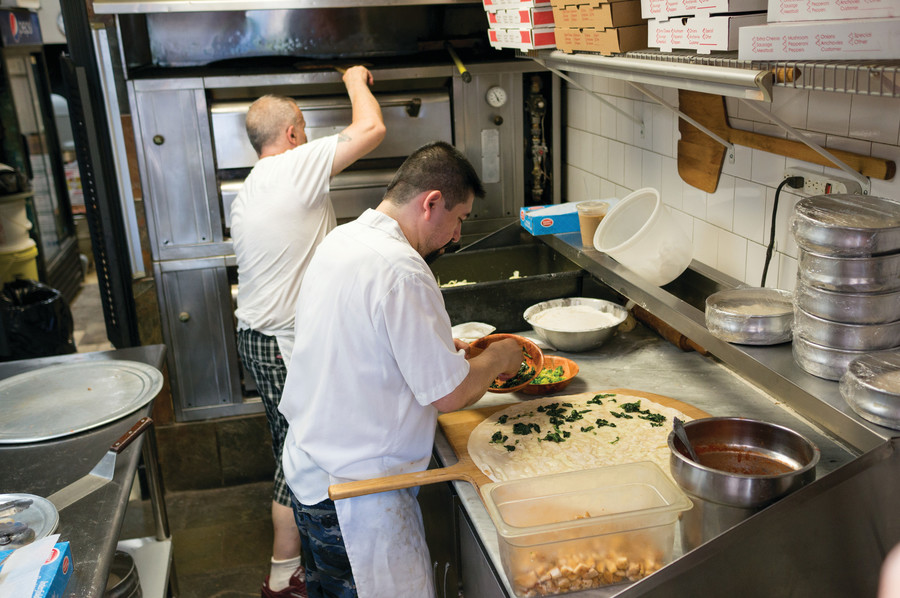 Employees at Famous Pizza Express prepare a pizza and prep the oven during the lunch rush.