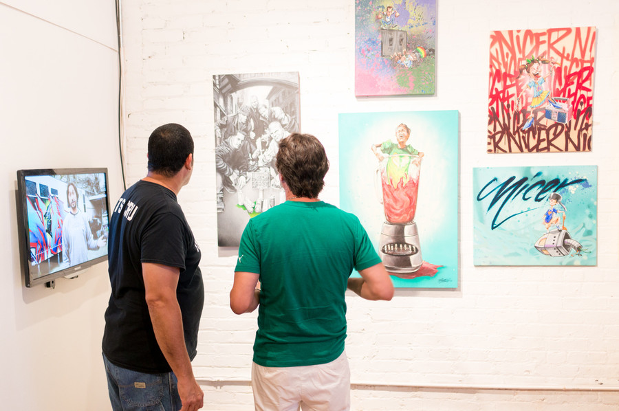 Wilfredo Feliciano, known as 'Bio,' left, and Hector Nazario, known as 'Nicer' from Tats Cru, look at some of their artwork at their exhibition in BronxArtSpace.